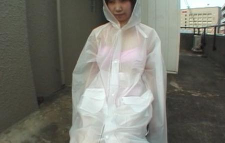 水着の上から雨合羽を着てフードまでかぶっている女性の画像
